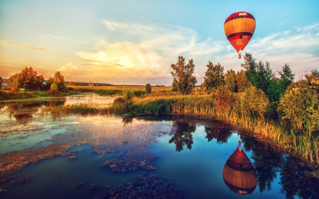 Beautiful fantasy sunrise summer landscape with lake and flying aerostat photo