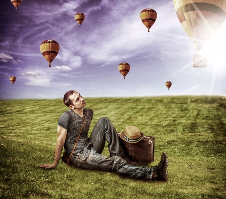 Young man traveler sitting on a fresh green grass and lookig to a flying balloons in blue sky photo