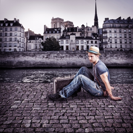 Retro photo of young handsome man traveller, sitting on the pavement promenade by the river in a European city photo