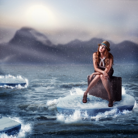 Woman traveller sitting on her suitcase in the sea Stock Photo