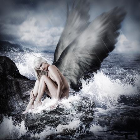 Sexy mooie blonde vrouw met engelenvleugels zittend op een rots in de zee in storm Stockfoto