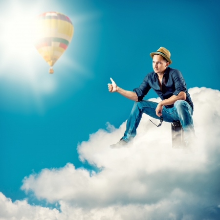 Young handsome man traveller sitting on a clouds with a sign hitch hiking photo