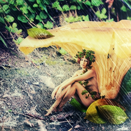 Rain in fantasy land. Young woman - Forest nymph sitting, hiding from the rain under the mushroom Stock Photo