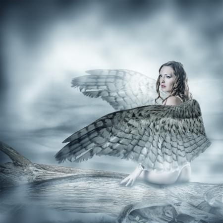 Sexy mooie vrouw met vogels vleugels met veren zitten op een boom