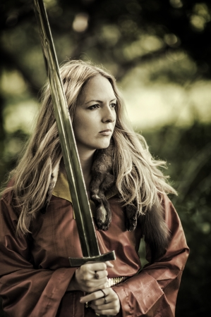 Beautiful blond sexy woman warrior with sword outdoor Standard-Bild