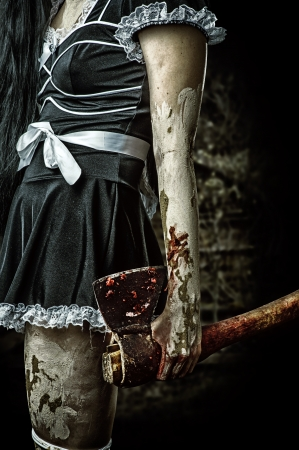 Horror. Dirty womans hand holding a bloody ax outdoor in night forest
