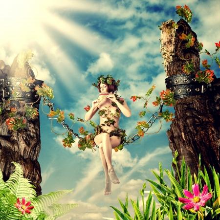 Joven y bella mujer de hadas tocando la flauta mientras está sentado en un columpio en la cadena entre las rocas y las hojas