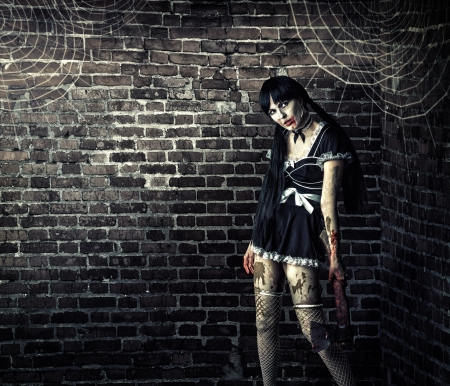 Horror. Sexy dirty woman zombie  holding a bloody ax  写真素材