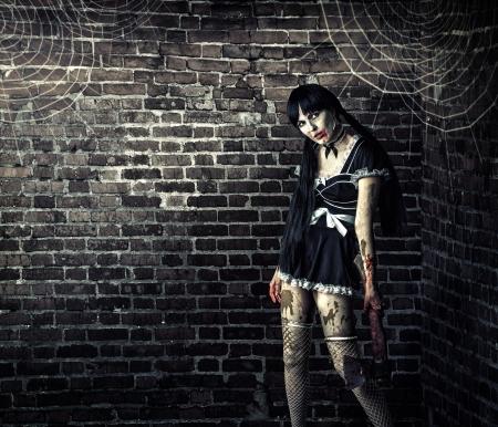 Horror. Sexy vuile vrouw zombie met een bloedige bijl