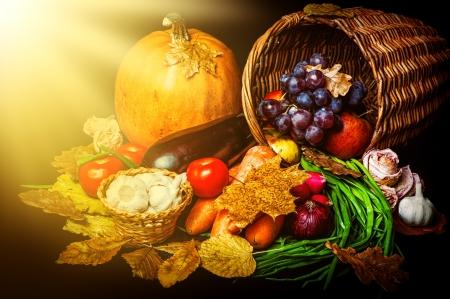 野菜と黒の背景に太陽の光と葉の美しい秋の収穫 写真素材