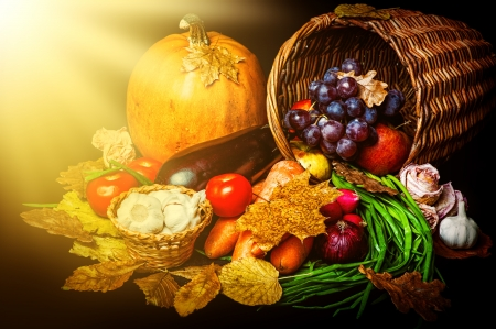cornucopia: Beautiful autumn harvest of vegetables and leaves on black background with sun light