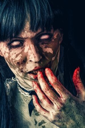 Scary zombie vrouw met witte ogen en bloedige hand