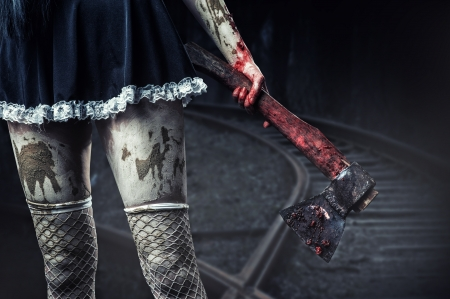 Horror. Dirty womans hand holding a bloody axe outdoor in night forest