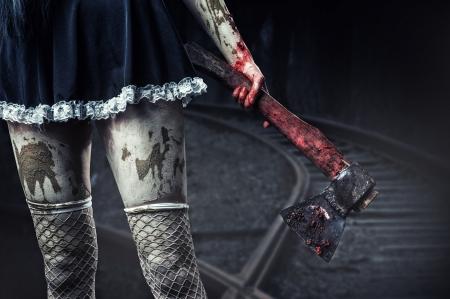 Horror. Hand houden van een bloedige bijl outdoor in nachtbos vuile vrouw
