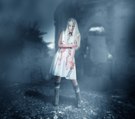 Sexy woman zombie stands among the ruins in the mist and moonlight photo