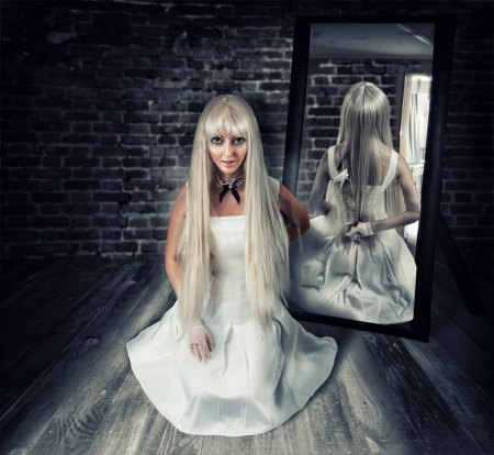 woman knife: Young beautiful blond woman sitting on wooden floor in old dark room with big knife in mirror reflection