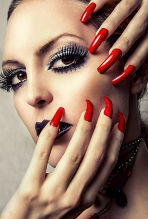 vamp: Beauty woman with perfect gothic makeup  Beautiful Professional Holiday Make-up and long false red Nails