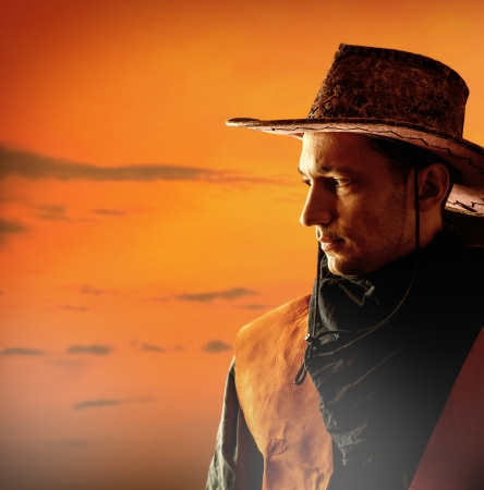 Amerikaanse cowboy in bruine hoed op een zonsondergang achtergrond buiten