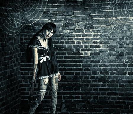 Horror Sexy vuile vrouw zombie met een bloedige bijl Stockfoto