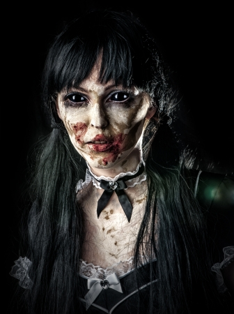 Scary zombie woman  with black eyes and bloody mouth photo