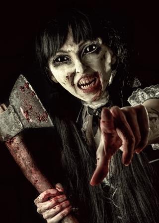 血まみれの斧で死んだ女性ゾンビ撮影に手を拡張します。ハロウィーンのコンセプトです。あなたを指している邪悪な幽霊