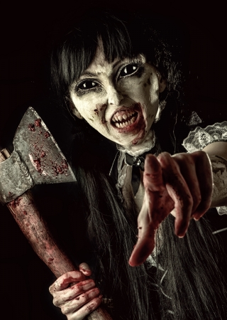Dead female zombie with bloody axe extends hand to shot. Halloween concept. Evil ghost pointing at you photo