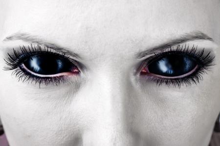 Evil black female alien, vampire or zombie eyes. dirt make up. Macro. Halloween theme  photo
