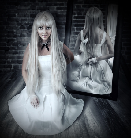 Young beautiful blond woman sitting on wooden floor in old dark room with big knife in mirror reflection photo