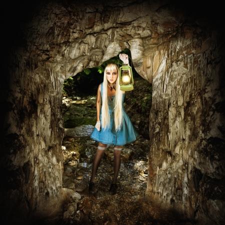 Adventure concept. Woman traveller covers her way lantern (kerosene lamp) in a dark cave Stock Photo - 21965019