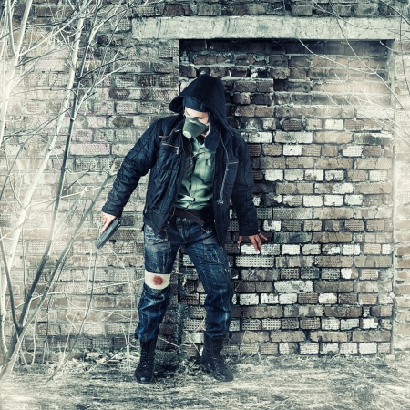 Environmental disaster. Post apocalyptic survivor in gas mask holding hand gun photo