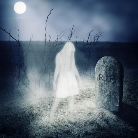 Permanecer Mujer Fantasma blanco en su tumba en el cementerio viejo photo