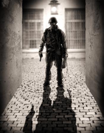 Horror. silhouet van een gevaarlijke militaire mannen met hand pistool in de steeg bij het licht van een lantaarn in de nacht