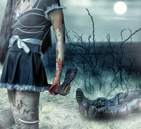 ハロウィーンの恐怖の概念。女性ゾンビの手で斧を保持します。バック グラウンドで死体の男の足があります。 写真素材