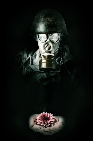 Concept. Hope after environmental protection. Man in gas mask holding flower in palms photo