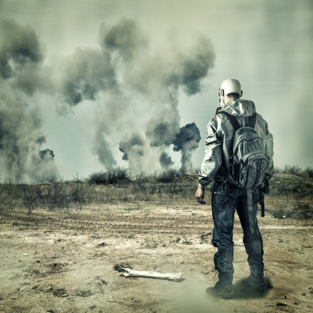 Post apocalypse. Man in gas mask with handgun and  back pack in apocalyptic world looking on explosions on horizon