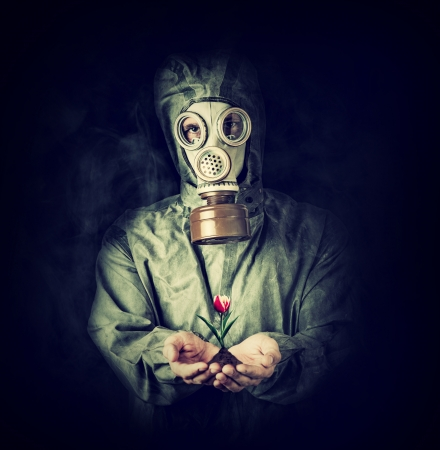 Concept. Hope after environmental protection. Man in gas mask holding tulip flower in palms