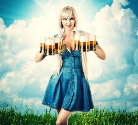 young sexy oktoberfest woman wearing a dirndl holding six beer mugs. outdoor background with grass and sky Standard-Bild