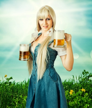 young sexy oktoberfest woman wearing a dirndl holding two beer mugs