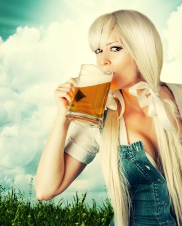 Mooie oktoberfest jonge sexy vrouw die een dirndl bier drinken uit beker outdoor Stockfoto
