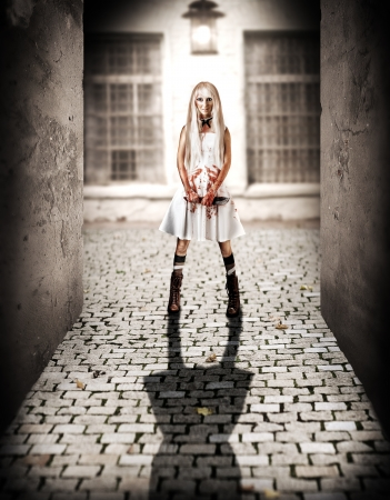 Halloween Horror concept  Young woman killer with big knife in hands stay in the alley by the light of a lantern at night and smiling photo