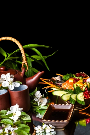 Asian Teapot  with jasmine flowers and food on black background with copyspace photo