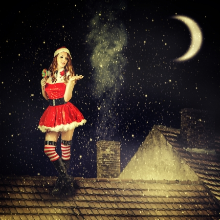 stay beautiful: beautiful sexy christmas fairy woman  in red dress and in santa hat stay on tiled roof of house at magic night