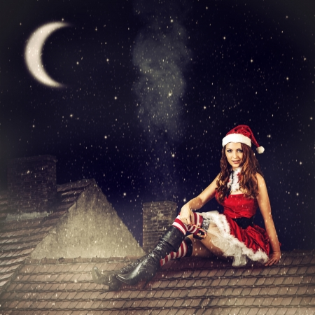 beautiful sexy christmas fairy woman  in red dress and in santa hat sitting on tiled roof of house at magic night photo