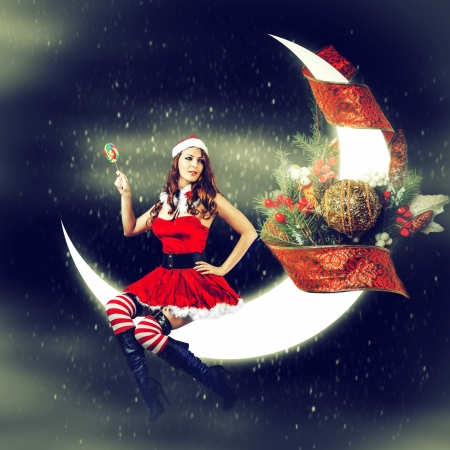 Kerstkaart. Jonge sexy mooie vrouw in santa claus kleding zittend op een maan met kerstversiering