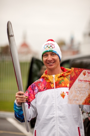 KOLOMNA - OCTOBER 10: Aleksey Kolesnikov - Russian champion in freestyle motocross carrying Olympic torch, on October 10, 2013 in Kolomna, Russia