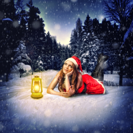 santa costume: Christmas card design - beautiful woman - santa claus lies in the snow forest