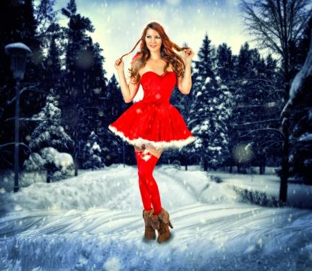 stay beautiful: Tarjeta de Navidad desighn - hermosa mujer sexy con atuendos de santa claus permanecer en el bosque de la nieve