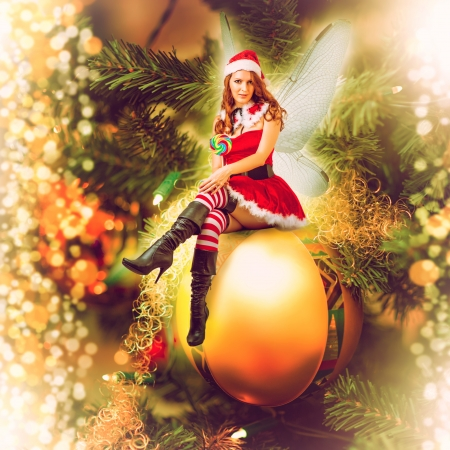 xmas card: Fairy christmas woman wearing santa claus clothes with wings sitting on a decorative ball on a christmas eve tree