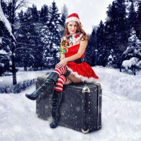 Christmas travel concept  Young sexy woman wearing santa claus clothes sitting on a big retro suitcase in the snow forest photo