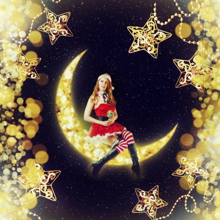 Fantasy magic christmas card - beauty woman santa claus sitting on a moon in night sky with stars and beads christmas decorations photo